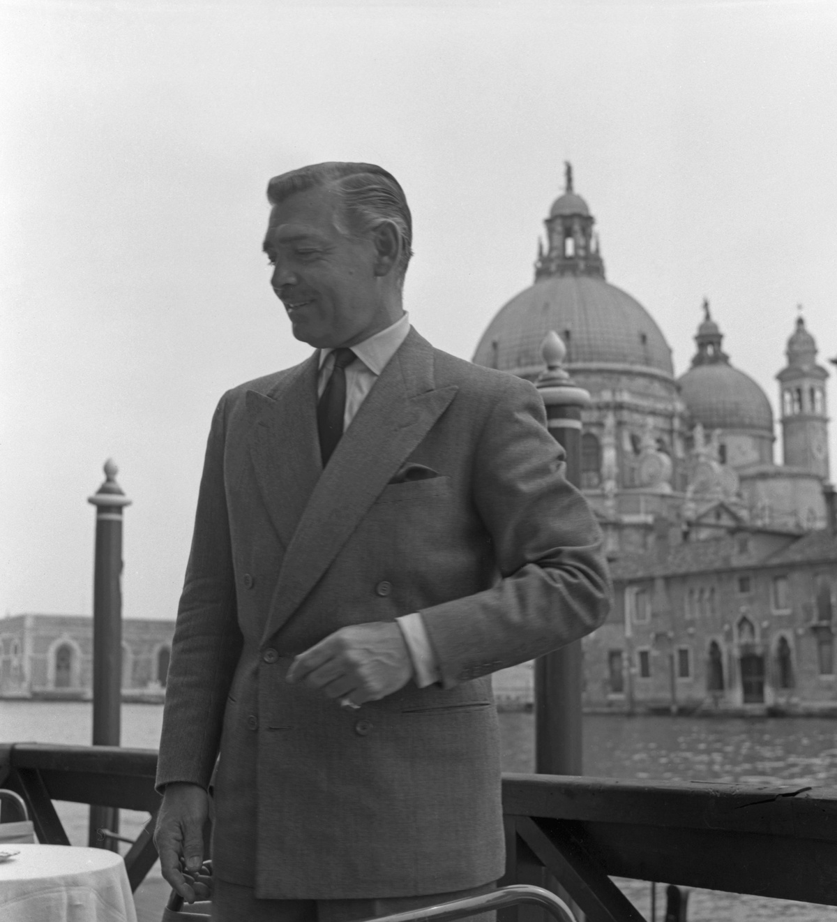 American actor Clark Gable, wearing a suit and a tie, portrayed standing on a restaurant terrace, on the background the Salute Basilica, Venice, 1953. КРЕДИТ s